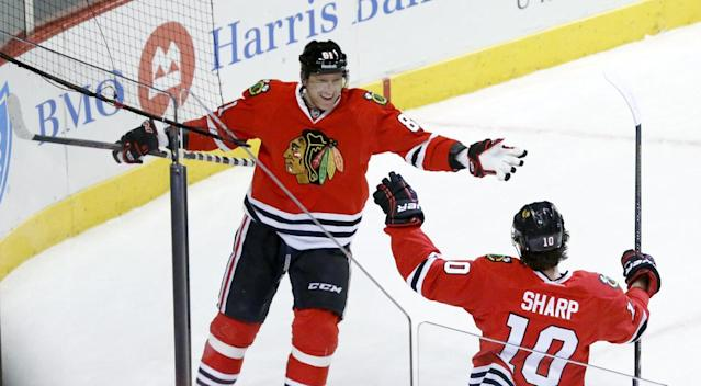 Chicago Blackhawks left wing Patrick Sharp (10) celebrates his goal with right wing Marian Hossa (81) during the first period of an NHL hockey game against the New Jersey Devils, Monday, Dec. 23, 2013, in Chicago. (AP Photo/Charles Rex Arbogast)
