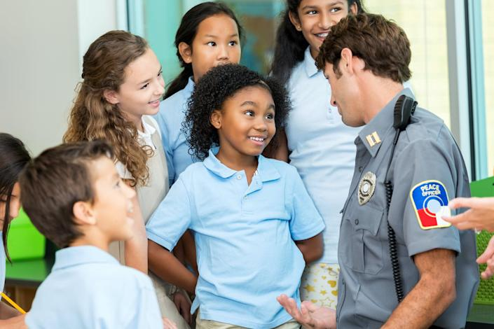 """<span class=""""caption"""">The image police project in schools doesn't always mirror reality.</span> <span class=""""attribution""""><a class=""""link rapid-noclick-resp"""" href=""""https://www.gettyimages.com/detail/photo/elementary-school-student-asks-policeman-a-question-royalty-free-image/596374182"""" rel=""""nofollow noopener"""" target=""""_blank"""" data-ylk=""""slk:SDI Productions"""">SDI Productions</a></span>"""