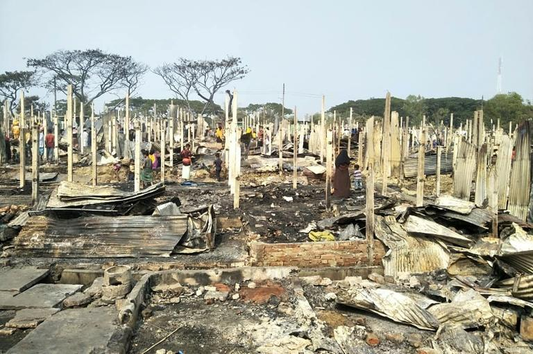 Rohingya refugees sift through the ashes after a fire broke out at Nayapara refugee camp in Teknaf, south of Cox's Bazar, on January 14, 2021