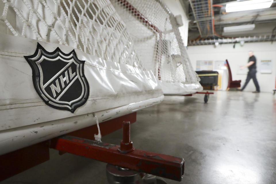 FILE - In this March 12, 2020, file photo, goals used by the NHL hockey club Nashville Predators are stored in a hallway in Bridgestone Arena in Nashville, Tenn. A year after the worldwide coronavirus pandemic stopped all the games in their tracks, the aftershocks are still being felt across every sector. (AP Photo/Mark Humphrey, File)