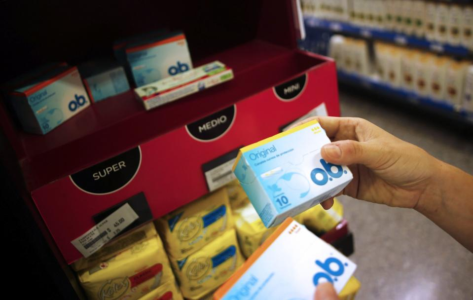 A woman takes tampon boxes out of a supermarket shelf in Buenos Aires January 16, 2015. Argentines have been complaining for a while now about the country's product shortages. And, until recently, the government has managed to brush aside such complaints, which have centered around Argentina's import restrictions. Well until, that is, the country's 20.6 million women couldn't find their favorite tampons earlier this month, during the height of summer. REUTERS/Marcos Brindicci (ARGENTINA - Tags: POLITICS BUSINESS SOCIETY)