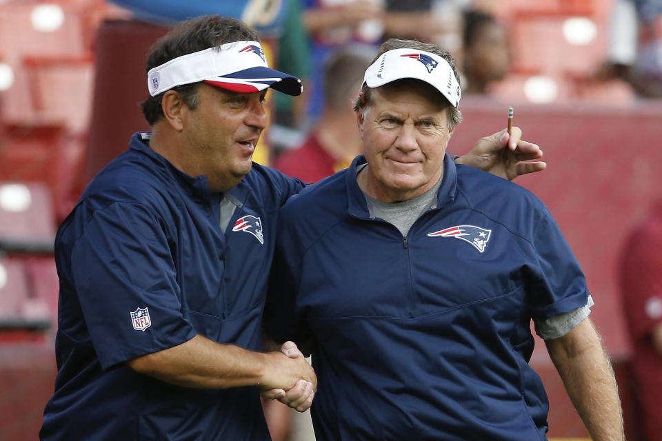 Michael Lombardi, assistant to the coaching staff of the New England Patriots, shakes hands with head coach Bill Belichick before a preseason game against the Washington Redskins in Landover, Md., on Aug. 7, 2014. (AP/Alex Brandon)