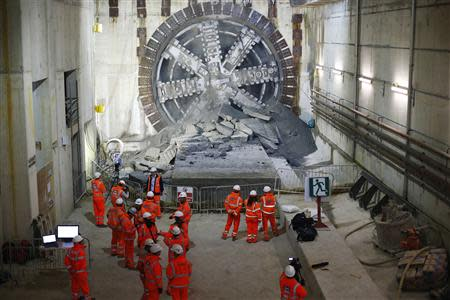 Workers look on after a tunnelling machine made the breakthrough into the station structure at Canary Wharf, in east London June 11, 2013. REUTERS/Andrew Winning