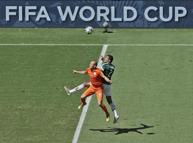 Netherlands' Arjen Robben, left, and Mexico's Francisco Rodriguez go for a header during the World Cup round of 16 soccer match between the Netherlands and Mexico at the Arena Castelao in Fortaleza, Brazil, Sunday, June 29, 2014. (AP Photo/Themba Hadebe)