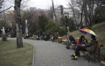 People, some wearing masks to help protect against the spread of coronavirus, sit in a public garden hours before a two-day weekend curfew, in Ankara, Turkey, Friday, Feb. 12, 2021. Turkey's Health Minister Fahrettin Koca sais Wednesday the country has reached an agreement to purchase another 50 million doses of the COVID-19 vaccine produced by China's Sinovac company, bringing the total amount to 100 million doses. (AP Photo/Burhan Ozbilici)