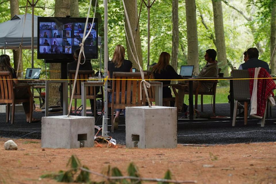 Bridgewater's famous Monday morning meetings now include 25 people congregated under the main tent, plus more than 100 others on Zoom; here, founder Ray Dalio can be seen joining the call, in the upper right corner.