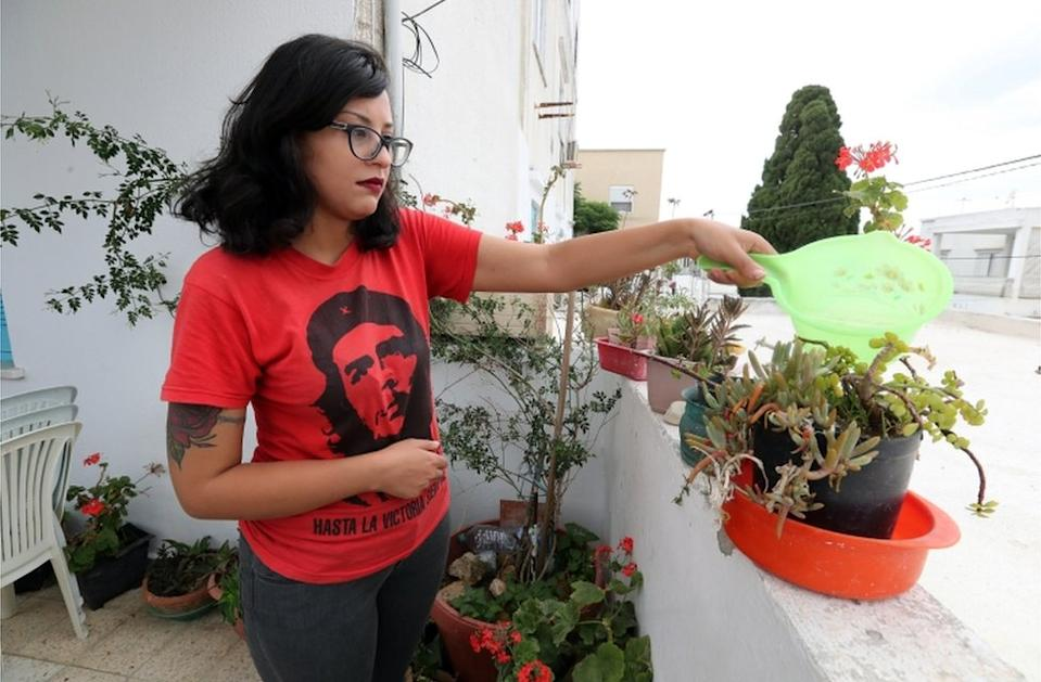 Emna Charqui waters plants on a balcony in Tunis on Wednesday. The 27-year-old has been sentenced to six months in prison, after sharing a satirical Facebook post about hand-washing that imitated Koranic verse.