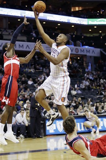 Charlotte Bobcats' Boris Diaw, of France, center, drives past Washington Wizards' Jan Vesely, bottom right, and John Wall, left, during the first half of an NBA basketball game in Charlotte, N.C., Saturday, Jan. 28, 2012. (AP Photo/Chuck Burton)