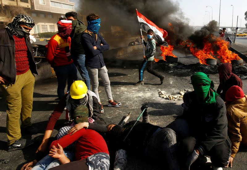 Iraqi demonstrators sit on the street near burning tires blocking a road during ongoing anti-government protests in Najaf