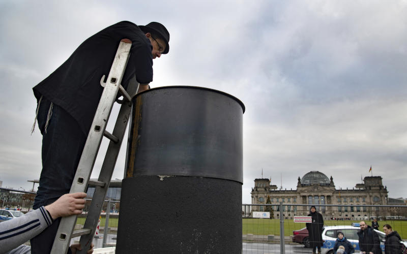 """The author Eliyah Havemann reattaches a previously dismantled steel plate to the controversial steel column of the artists' collective """"Centre for Political Beauty"""" (ZPS) opposite the Reichstag building in Berlin Germany, Sunday, Jan.5, 2019.  Several activists have tried to dismantle the controversial steel column of the artists' collective """"Centre for Political Beauty"""" (ZPS) in Berlin. """"One should not make art and politics with ashes of victims of the Holocaust,"""" Havemann told the dpa on Sunday, explaining the reasons. The police stopped the action and ZPS filed a complaint. (Paul Zinken/dpa via AP)"""