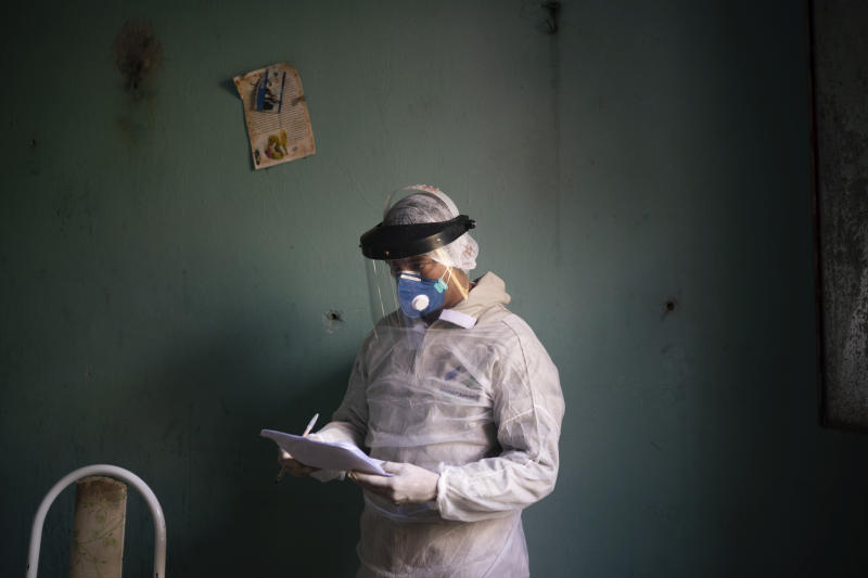Health worker Ari Nascimento takes notes as he prepares to collect material for a COVID-19 test of an elderly woman in Manacapuru, Amazonas state, Brazil, Wednesday, June 3, 2020. (AP Photo/Felipe Dana)