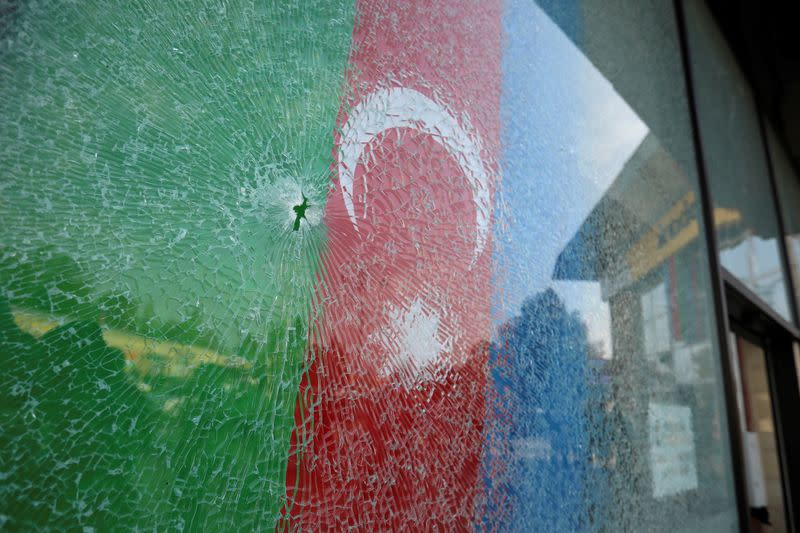 A view shows an Azerbaijani flag behind a damaged window in Barda