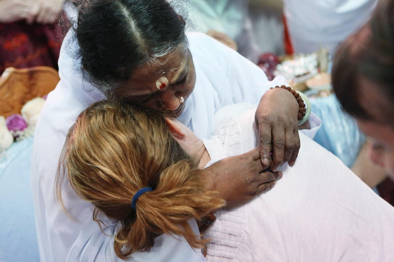 """Mata Amritanandamayi, also known as """"The Hugging Saint"""" embraces a follower on July 10, 2012 in New York City. The Hindu spiritual leader and guru is on a 10-city U.S. tour, where she is expected to bless thousands of people individually at free public """"darshan"""" gatherings. Amritanandamayi, 58, from India's southern state of Kerala, is considered a living saint by her followers, who refer to her as """"Amma"""" or mother. She has been giving the public """"darshan"""" gatherings for 35 years, with the aim of bringing good fortune, well-being and grace to her followers through her embrace. Participants are encouraged to donate to her global charitable organizations, known collectively as """"Embracing the World.""""  (Photo by John Moore/Getty Images)"""