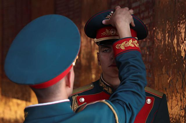 A standing guard soldier gets his hat adjusted by his chief at the Mamayev Kurgan World War Two memorial complex in Volgograd, Russia, June 21, 2018. As well as shooting all the matches, Reuters photographers are producing pictures showing their own quirky view from the sidelines of the World Cup. REUTERS/Sergio Perez