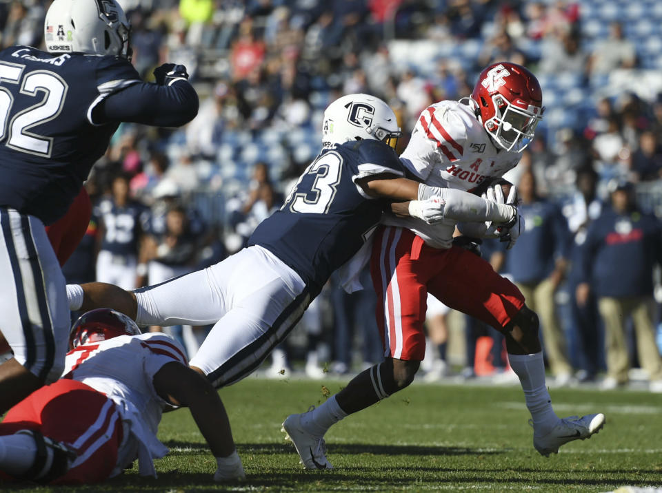 Houston wide receiver Bryson Smith is tackled by Connecticut linebacker Jackson Mitchell (43) in the second half of an NCAA college football game, Saturday, Oct. 19, 2019 in East Hartford, Conn. (AP Photo/Stephen Dunn)