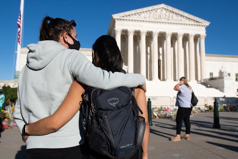Voters embrace near a makeshift memorial for Rutth Bader Ginsburg at the US supreme court in Washington DC, on 21 September.