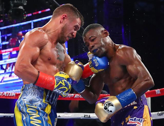 Vasyl Lomachenko lands a left on Guillermo Rigondeaux's chin during his six-round TKO victory in their WBO junior lightweight title bout Saturday in New York. (Mikey Williams/Top Rank)