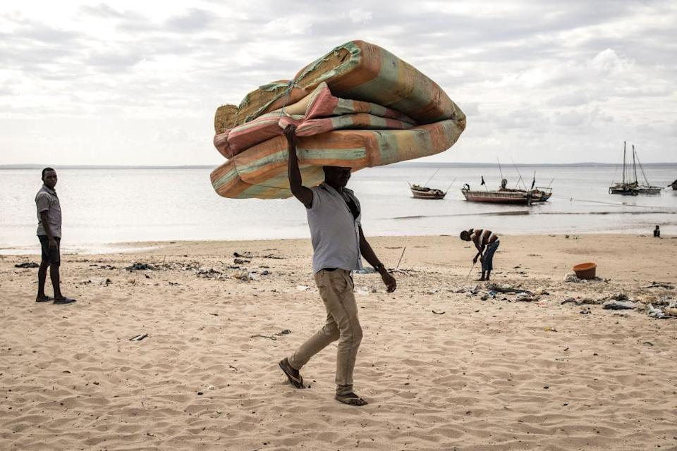 A man carries a mattress as he arrives at Paquitequete beach in Pemba, after fleeing Palma by boat with 49 other people.