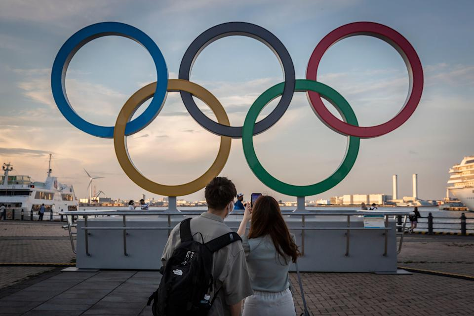People take photographs of Olympics rings.