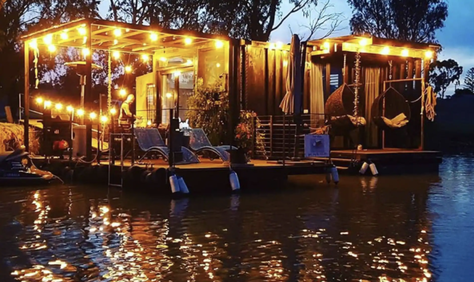 'The Cube', a floating guesthouse, lit up with outdoor lights on Adelaide's Murray River in Western Australia at dusk