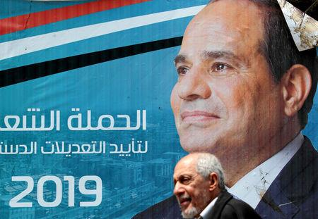 FILE PHOTO: A man walks in front of a banner depicting Egyptian President Abdel Fattah al-Sisi before the upcoming referendum on constitutional amendments in Cairo