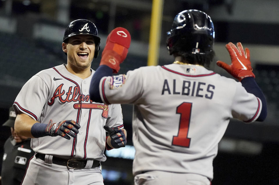 CORRECTS TO AUSTIN RILEY NOT FREDDIE FREEMAN - Atlanta Braves' Austin Riley, left, laughs as Ozzie Albies (1) waits to congratulate him after he hit a two-run home run against the Arizona Diamondbacks during the third inning of a baseball game Thursday, Sept 23, 2021, in Phoenix. (AP Photo/Darryl Webb)