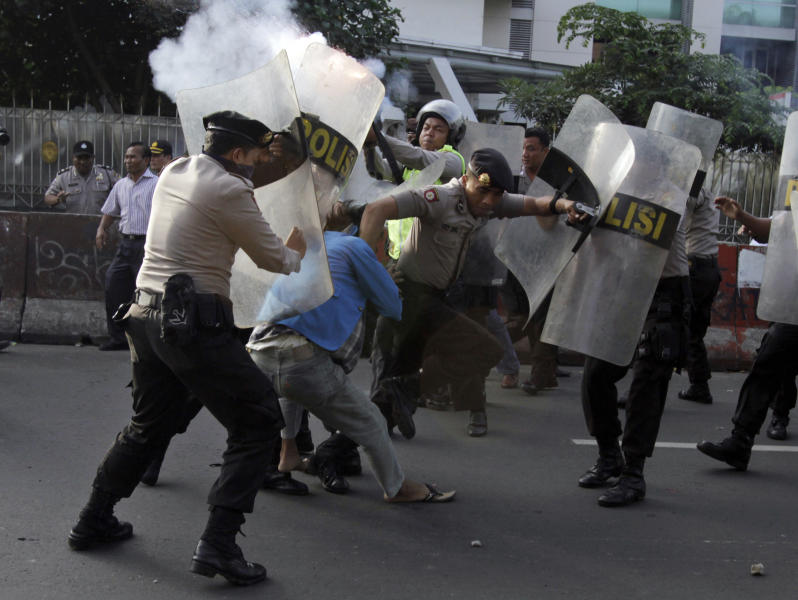 Indonesian police officers try to catch students during a protest against price hikes on fuel, in Jakarta, Indonesia, Wednesday, March 14, 2012. (AP Photo/Achmad Ibrahim)
