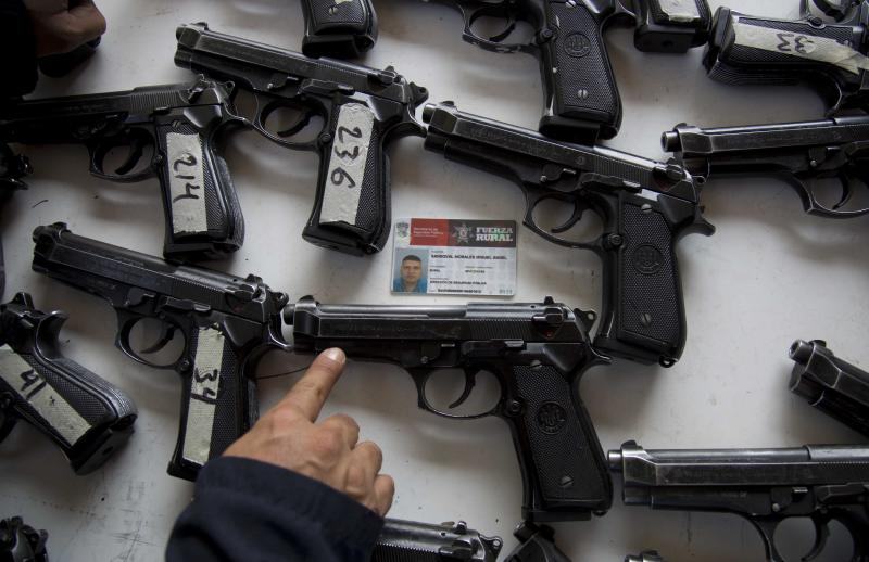 A federal police looks for the assigned weapon that corresponds to the rural police's identification card before the start of a ceremony in Tepalcatepec, Mexico, Saturday, May 10, 2014. At the ceremony in the town where the vigilante movement began in February 2013, officials handed out new pistols, rifles and uniforms to 120 self-defense group members who were sworn into a new official rural police force. Mexico's government on Saturday began demobilizing the vigilante movement of assault-rifle-wielding ranchers and farmers that had succeeded in largely expelling the Knights Templar cartel from the western state of Michoacan when authorities couldn't. (AP Photo/Eduardo Verdugo)