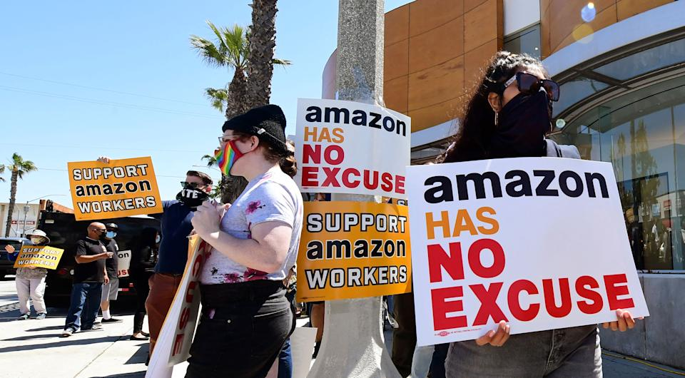 Supporters of Amazon workers protest in front of Fidelity Investments, one of the company's largest shareholders on May 24, 2021 in Santa Monica, California. - The nationwide protests are asking shareholders to demand that Amazon change its practices to be more accountable to workers, communities and stakeholders, while also calling on Amazon to cut ties with US Immigration and Customs Enforcement and end its anti-competitive monopoly practices. (Photo by Frederic J. BROWN / AFP) (Photo by FREDERIC J. BROWN/AFP via Getty Images)