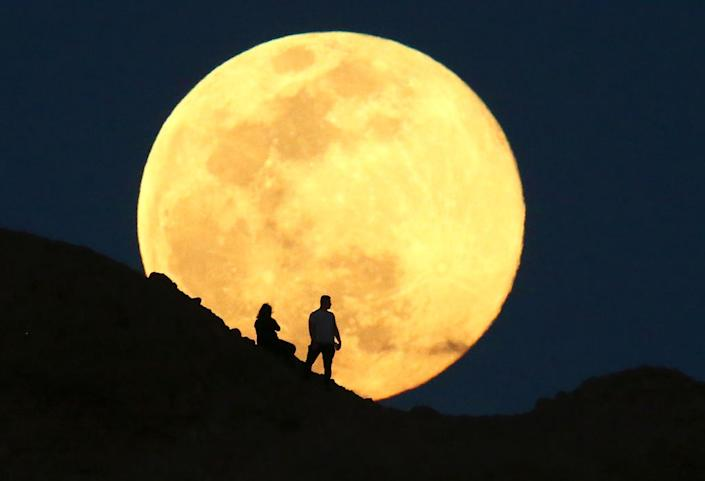 The supermoon, also known as the pink moon rises over the Papago Park Buttes on April 7, 2020 in Phoenix, Arizona.