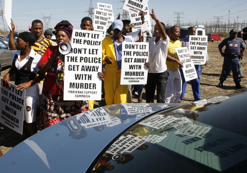 A group of protestors holds placards as a large crowd followed retired judge Ian Farlam and his team as they inspected the area where the bodies of mine workers were found after the shootings at Lonmin's platinum mine in Marikana near Rustenburg, South Africa, Monday, Oct. 1, 2012. Farlam, is conducting an inquiry into the shootings at the platinum mine. (AP Photo/Themba Hadebe)