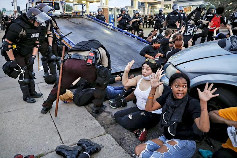 Protesters raise their hands on command from police as they are detained prior to arrest and processing at a gas station on South Washington Street, Sunday, May 31, 2020, in Minneapolis: AP