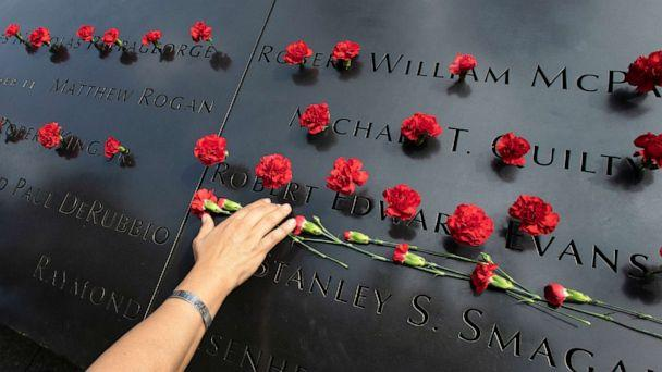 PHOTO: Norma Molina, of San Antonio, Texas, leaves flowers by the names of firefighters from Engine 33 at the September 11 Memorial, Sept. 9, 2019, in New York. (Mark Lennihan/AP, FILE)
