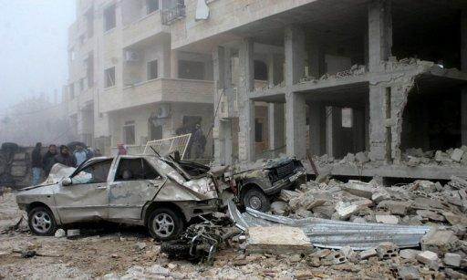 <p>A handout picture released by the Syrian Arab News Agency (SANA) shows Syrians inspecting the site of a suicide car bombing in Salmiyeh, a town in the central province of Hama, on January 22, 2013.</p>