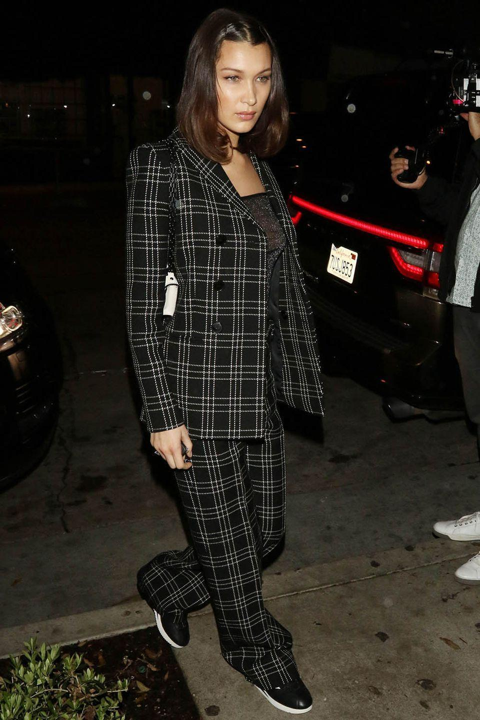 <p>In a plaid Dior suit from the French fashion house's fall 2018 collection, sheer top, white shoulder bag, and black sneakers while out in LA.</p>