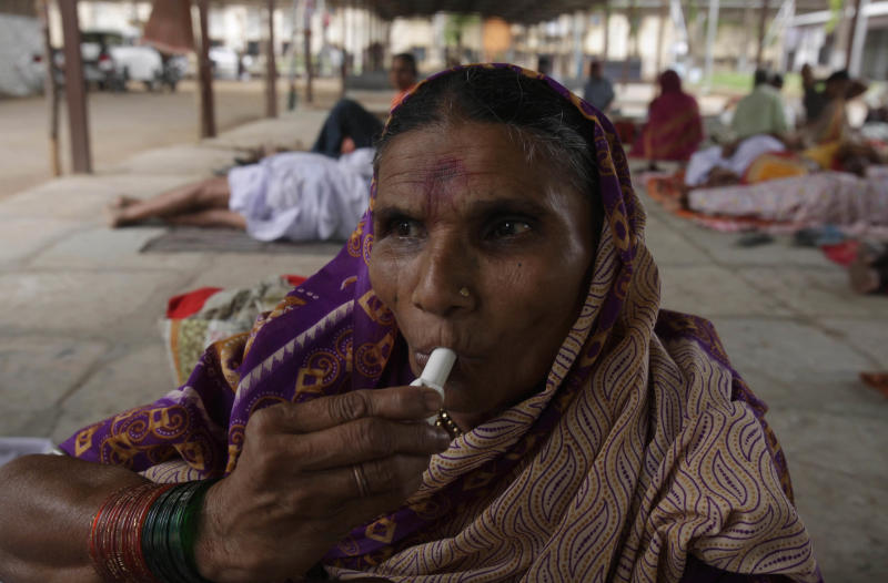 """Rukmini Bai, 57, from India's Maharashtra state uses an inhaler  as she waits to receive the"""" fish medicine"""" in Hyderabad, India, Tuesday, June 7, 2011.Every June, hundreds of thousands of asthma sufferers gather in Hyderabad to swallow live sardines smeared with secret herbs, convinced the ritual will cure them. The two day free treatment by the Goud family, which claims to have received the formula from a Hindu saint 162 years ago begins Wednesday. (AP Photo/Mahesh Kumar A.)"""