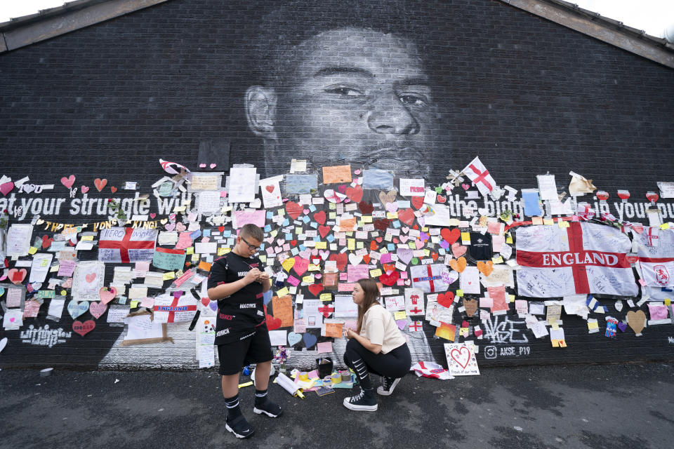 A boy stands by messages of support left on a mural of Manchester United striker and England player Marcus Rashford, on the wall of the Coffee House Cafe on Copson Street, in Withington, Manchester, England, Tuesday July 13, 2021. The mural was defaced with graffiti in the wake of England losing the Euro 2020 soccer championship final match to Italy. (AP Photo/Jon Super)