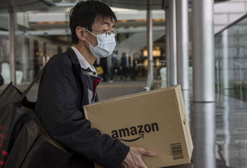 HONG KONG, CHINA - 2020/02/12: A man wearing a face mask holds a box of the American electronic commerce company Amazon in Central district, Hong Kong. The death toll from the covid-19 coronavirus epidemic passed 1, 100 and infected over 45, 000 people worldwide on February 12. (Photo by Miguel Candela/SOPA Images/LightRocket via Getty Images)