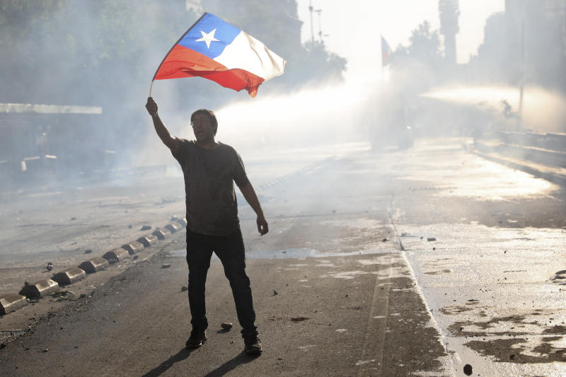 An anti-government protester waves a national flag in Santiago, Chile, Tuesday, Oct. 29, 2019. Chileans gathered Tuesday for a 12th day of demonstrations that began with youth protests over a subway fare hike and have become a national movement demanding greater socio-economic equality and better public services in a country long seen as an economic success story. (AP Photo/Rodrigo Abd)