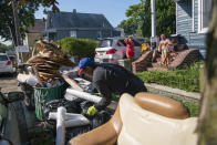 Residents watch a worker picking up debris, Monday, Sept. 6, 2021, in Passaic, NJ., from their flood damaged home in the aftermath of Hurricane Ida. (AP Photo/Eduardo Munoz Alvarez)