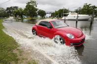 A passenger car drives through a road flooded by the Tchoutacabouffa River along Cedar Lake Road in Biloxi, Miss., Saturday, June 19, 2021, as water from Tropical Storm Claudette begins to recede. The storm brought much evening and early morning rain and flooded various communities along the Mississippi Gulf Coast. (AP Photo/Rogelio V. Solis)