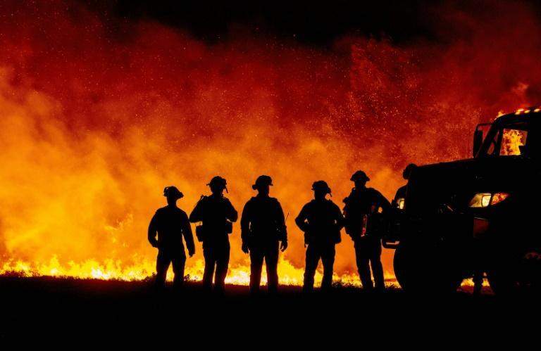 Fire fighters watch as flames quickly spread across a road at the Bear fire in Oroville, California in September 2020, one of a number of worsening disasters that experts have linked to climate change (AFP/JOSH EDELSON)