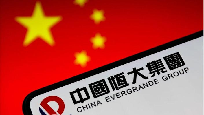 The evergrande logo is seen in front of a Chinese flag