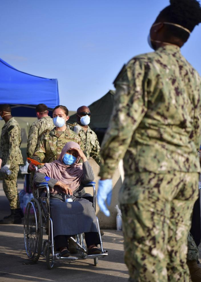 Senior Airman Romero, center, assists an Afghan evacuee at the Sigonella US air base, in Sicily, southern Italy, Sunday, Aug. 22, 2021. Some 662 people fleeing Afghanistan have arrived at the U.S. naval air base in Sicily as Washington tries to ramp up evacuations following the Taliban takeover of the country by using overseas military bases as temporary transit points. (US Naval Forces Europe-Africa via AP)