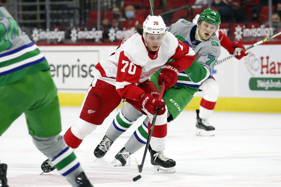 Detroit Red Wings' Troy Stecher (70) drives the puck after taking it away from Carolina Hurricanes' Steven Lorentz (78) during the first period of an NHL hockey game in Raleigh, N.C., Saturday, April 10, 2021. (AP Photo/Karl B DeBlaker)