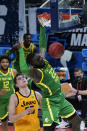 Oregon center Franck Kepnang (22) dunks on Iowa center Luka Garza (55) during the second half of a men's college basketball game in the second round of the NCAA tournament at Bankers Life Fieldhouse in Indianapolis, Monday, March 22, 2021. (AP Photo/Paul Sancya)