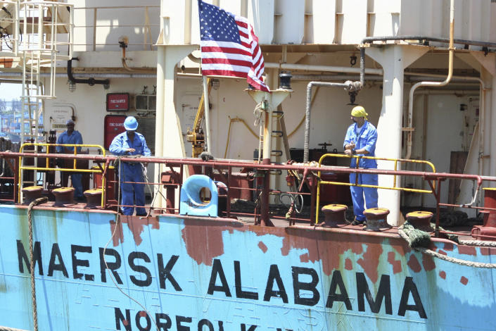 """FILE - In this Nov. 22, 2009 file photo, crew members work aboard the U.S.-flagged Maersk Alabama after the ship docked in the harbour of Mombasa, in Kenya. Police in the Indian Ocean island nation of Seychelles said Wednesday, Feb. 19, 2014 that two American security officers were found dead Tuesday in a cabin on the Maersk Alabama, the ship hijacked by pirates in 2009, an event dramatized in the movie """"Captain Phillips"""" starring Tom Hanks. (AP Photo, File)"""