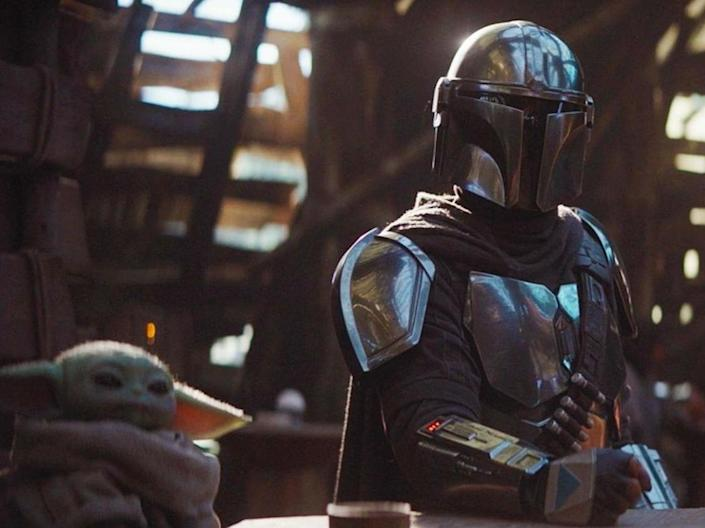 The Mandalorian (Pedro Pascal) sits with a tiny green companion in Disney's new Star Wars spin-off: Disney+