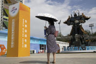 A visitor stands near a giant robot sculpture displayed at the venue for the China International Fair for Trade in Services (CIFTIS) to be held in Beijing on Friday, Sept. 4, 2020. As China recovers from the COVID-19 pandemic, business as usual is picking back up with the holding of the China International Fair for Trade in Services. Nearly 2,000 Chinese and foreign enterprises will participate and showcase their newest technology in public health and digital technology (AP Photo/Ng Han Guan)