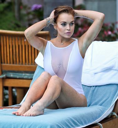 Lindsay Lohan showed off her curves in a sheer white one-piece swimsuit while she lounged at a Los Angeles pool